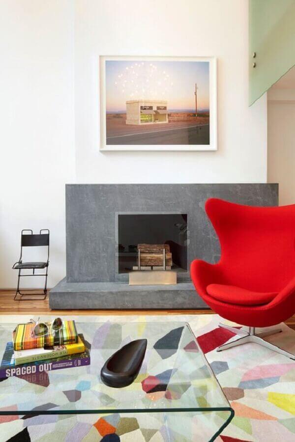 sala com lareira decorada com tapete e poltrona colorida Foto One Kindesign