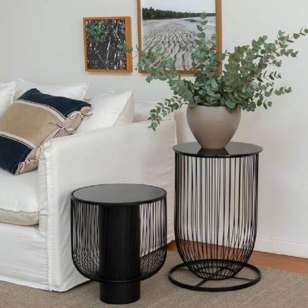 Sala decorada com sofá branco e mesa lateral alta preta