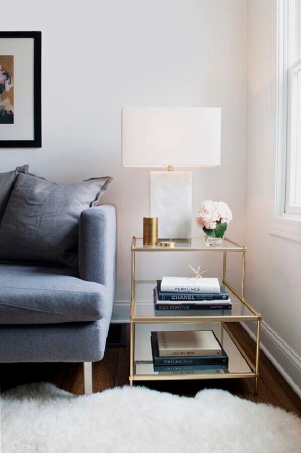 Sala de estar decorada com sofá cinza e mesa lateral alta de vidro