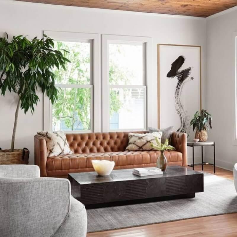 sala decorada com sofá marrom com acabamento capitonê  Foto Zin Home