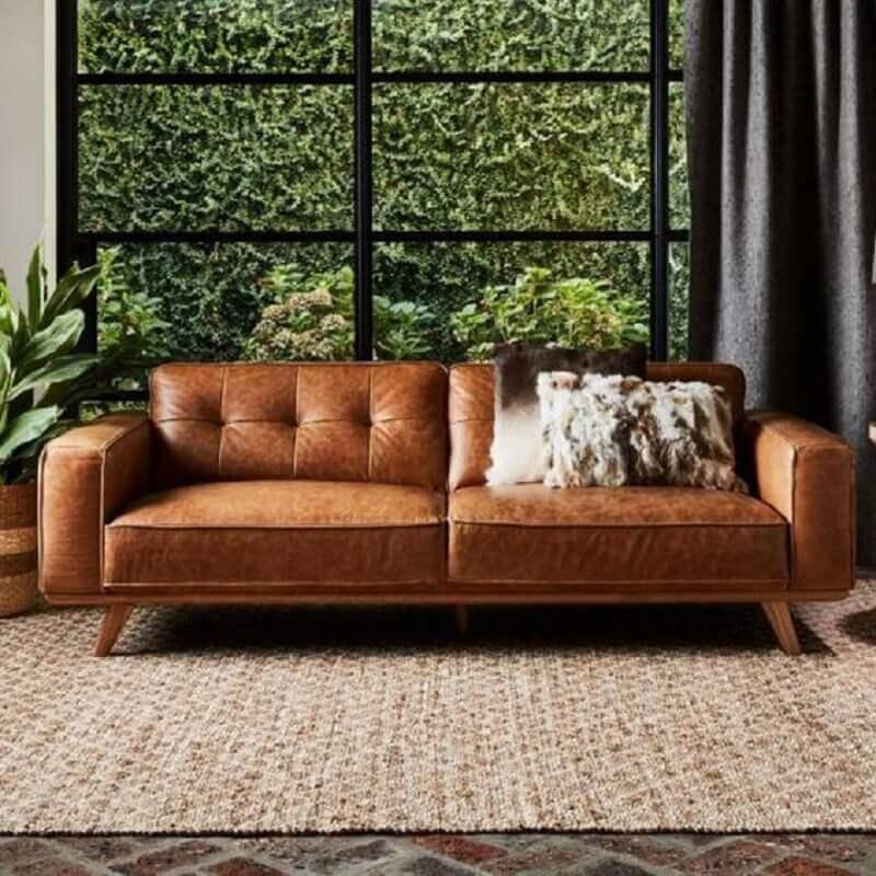 sala decorada com tapete rústico e sofá marrom de couro  Foto Architonic