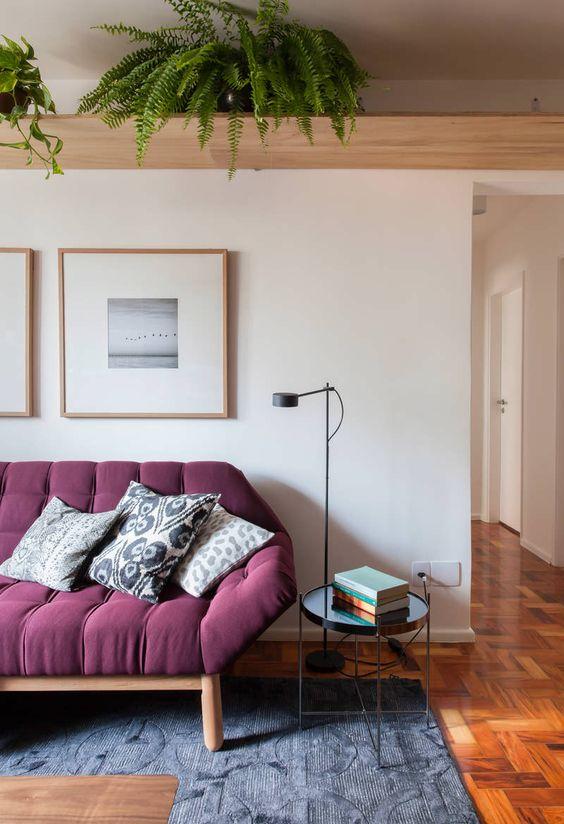 Sala roxa com sofá retrô e decoração clean