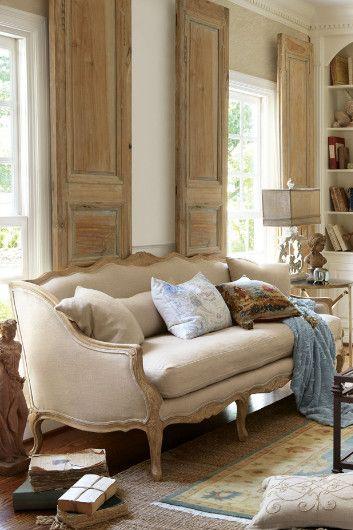 Sofá antigo bege com almofada azul clara