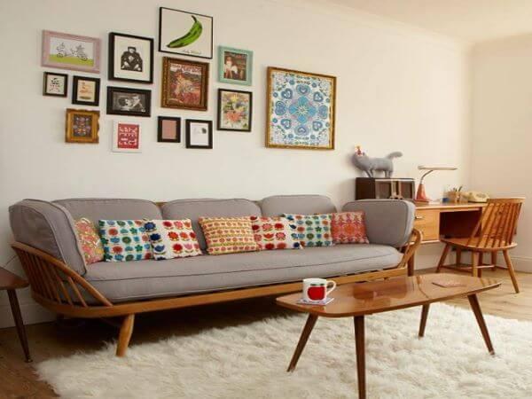 Sofá antigo de madeira com almofada estampada