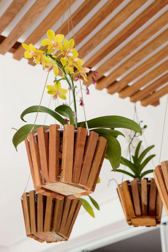 Vaso e madeira suspenso com flores
