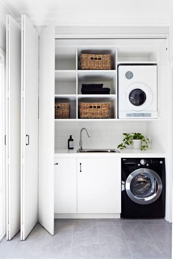 A área de serviço pequena e simples pode ser escondida por uma porta retrátil de madeira