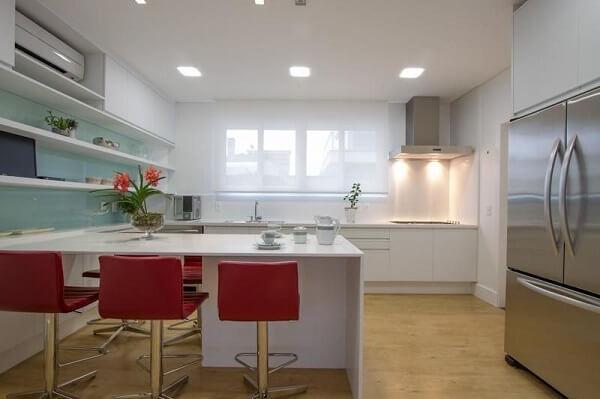 A bancada vermelha na cozinha clean quebra a neutralidade do espaço