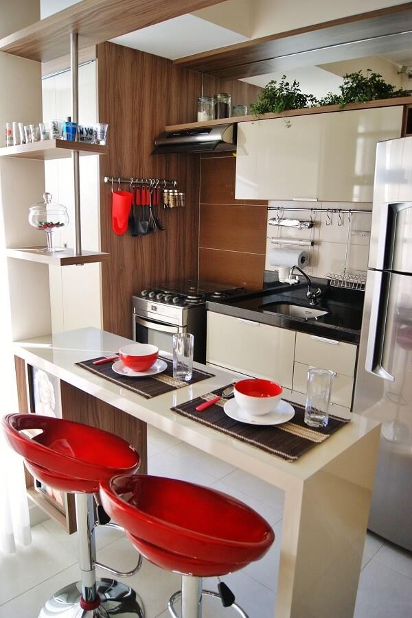A banqueta vermelha com encosto se contrasta com o armário neutro