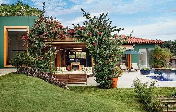 A pintura verde das casas de campo com varandas se harmonizam com a vegetação do entorno