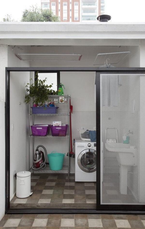 A porta de vidro separa essa área de serviço externa simples do restante da casa