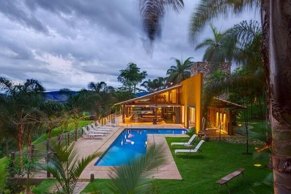Ambiente com fechamento de vidro traz uma outra perspectiva para as casas de campo com varandas e piscinas