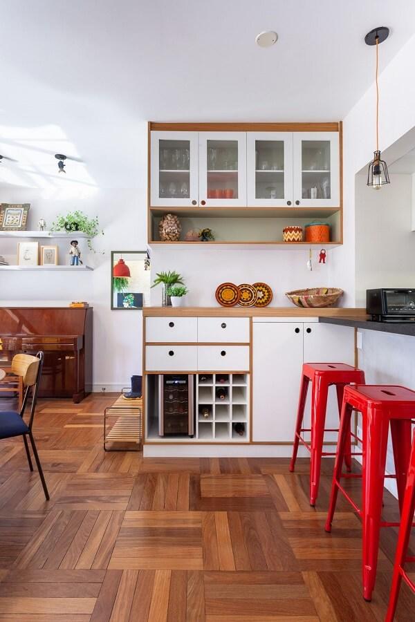Ambiente com móveis de madeira e banqueta vermelha para acomodar os moradores