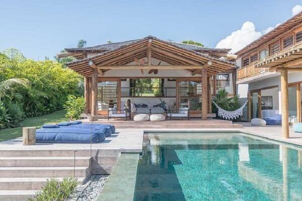 Ao invés de espreguiçadeiras, as casas de campo com varandas e piscinas podem ter colchões próximos a piscina