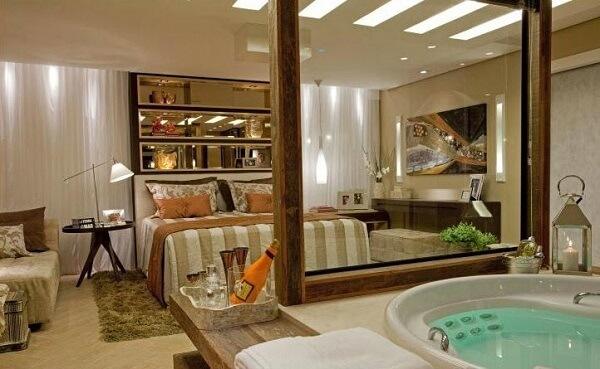 Aqui a divisória de vidro recebeu uma moldura de madeira e deixou o quarto com suíte ainda mais estiloso