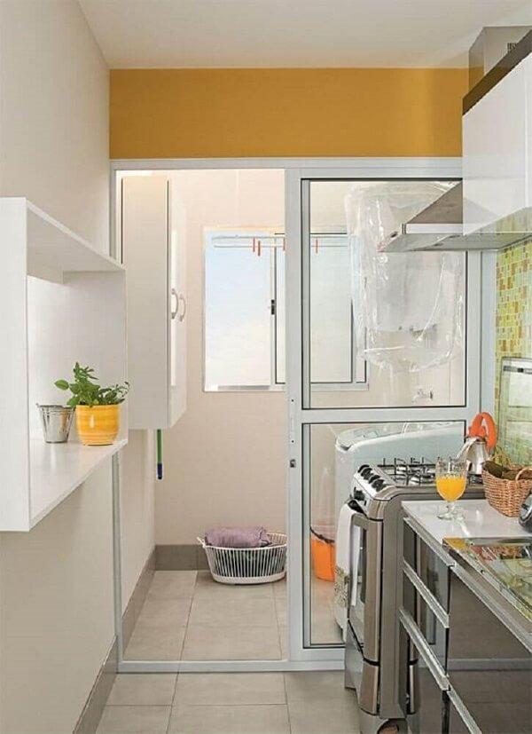 Aqui a porta de vidro separa a área de serviço da cozinha