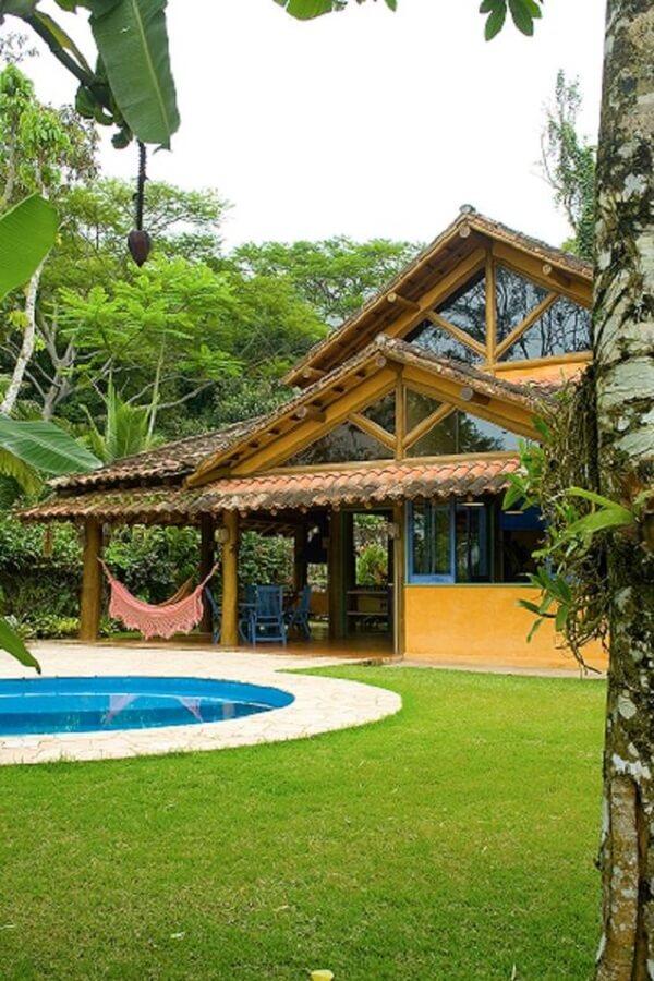 As colunas feitas de madeira e expostas se destacam nos projetos das casas de campo rústicas com varanda