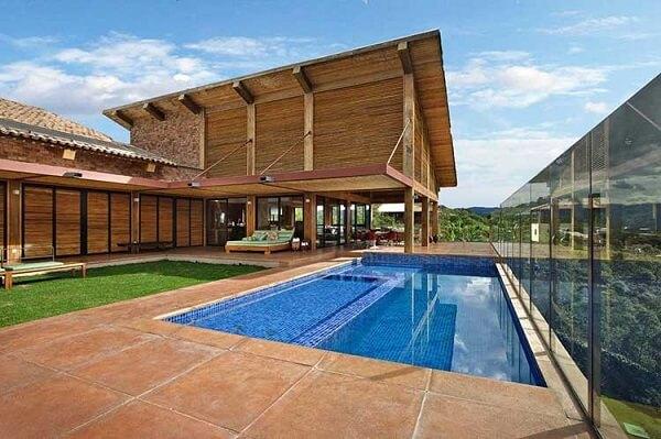 As piscinas também são muito bem vindas nos projetos de casas de campo com varanda e churrasqueira