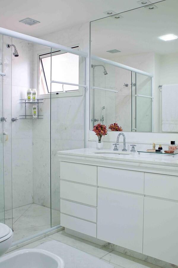 Banheiro clean com chuveiro cromado discreto
