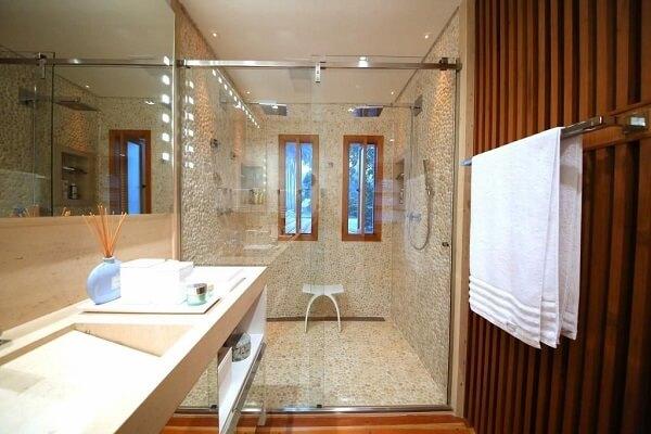 Banheiro com box de vidro e chuveiro cromado quadrado duplo