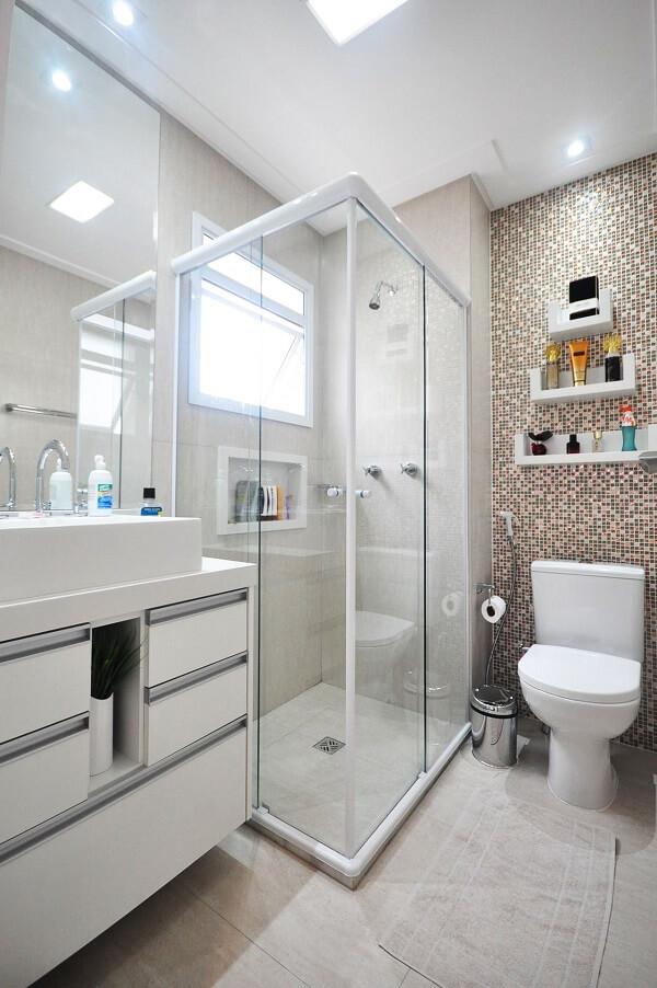 Banheiro com parede revestida com pastilhas e chuveiro cromado