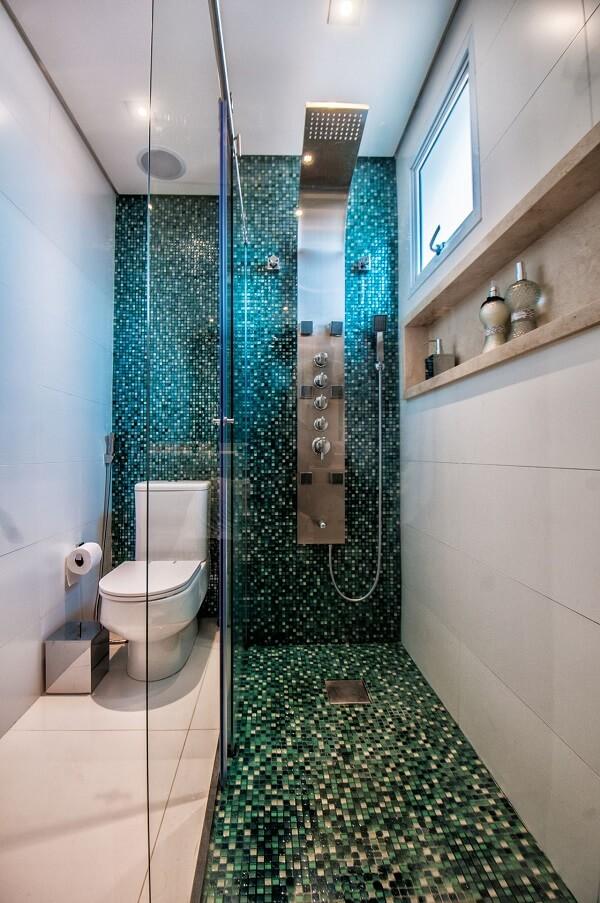 Banheiro com pastilhas de vidro e chuveiro cromado deslumbrante
