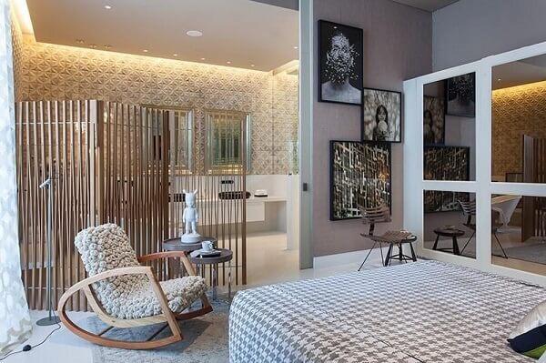 Cadeira de pelinho branco e banco de madeira decoram o quarto com suíte