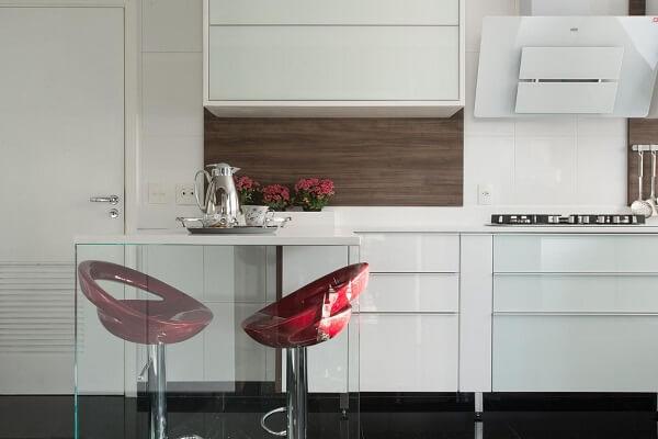 Cozinha planejada com bancada de vidro e banqueta alta vermelha