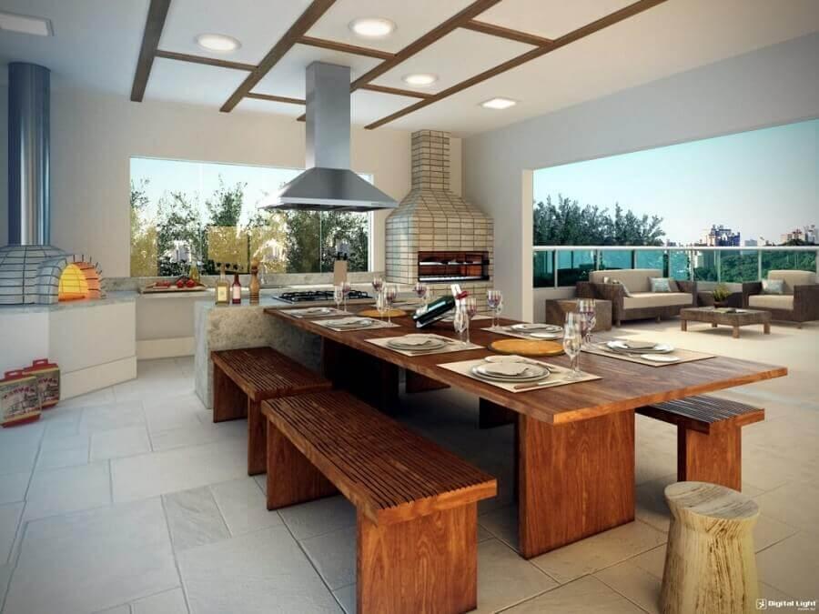 Decoração de cozinha gourmet externa com churrasqueira forno de pizza e mesa de madeira Foto Pinterest