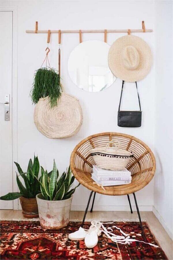 Hall com cadeira de vime e cabideiro de madeira com ganchos