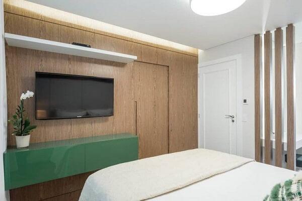 Modelo de quarto com suíte onde a porta do banheiro segue a mesma marcenaria do painel de TV