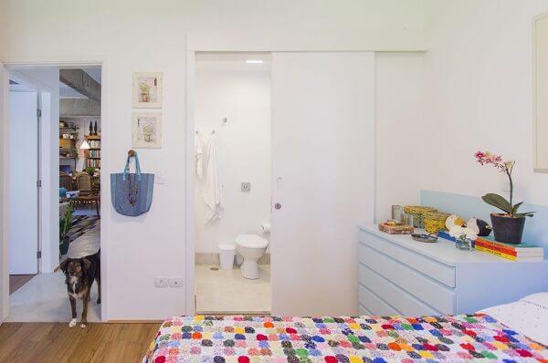 Nesse quarto com suíte simples a cômoda azul bebê se destaca