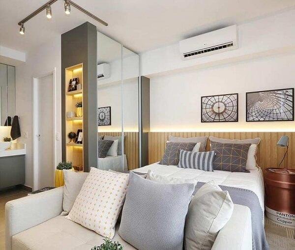 O armário espelhado ajuda na claridade dentro do quarto com suíte
