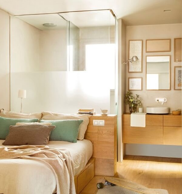 O banheiro foi estruturado atrás da cama de casal
