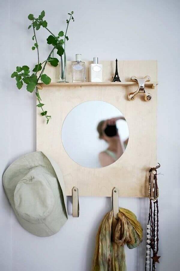 O espelho redondo no cabideiro de madeira traz um charme especial para o ambiente