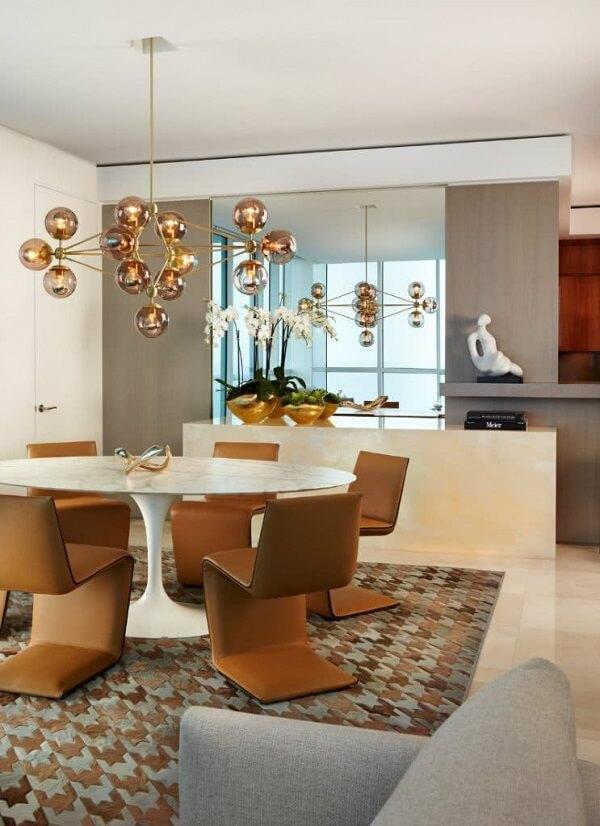 O lustre industrial cobre complementa com charme o ambiente da sala de jantar