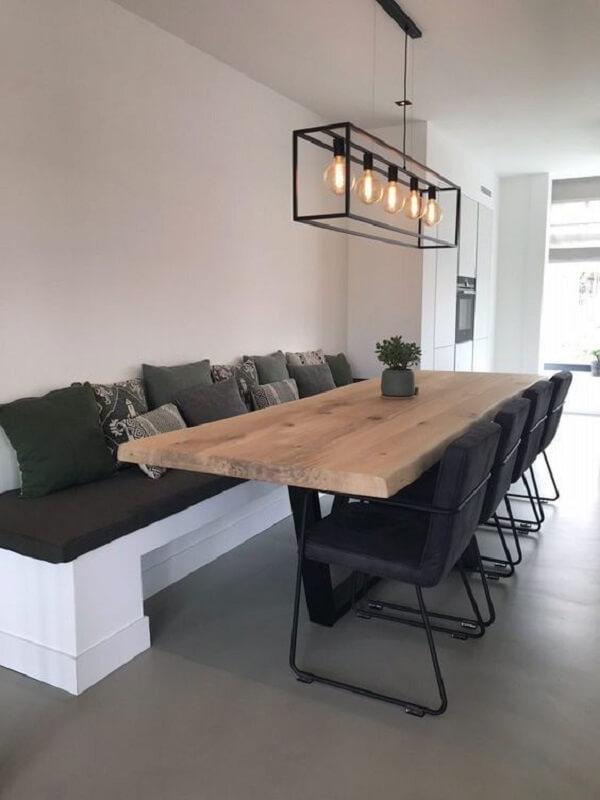 O lustre industrial preto traz um toque especial para a mesa de jantar de madeira