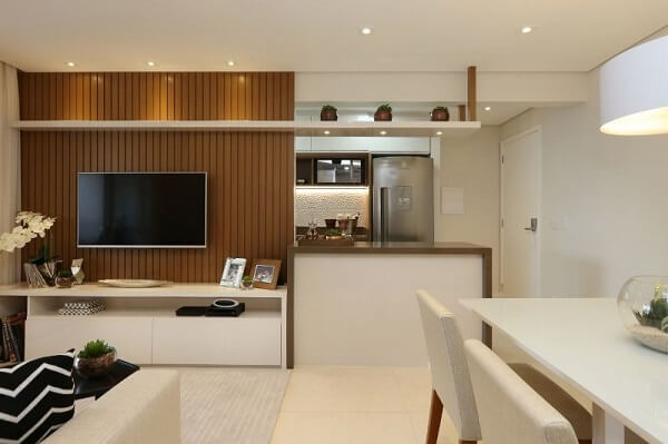 O painel ripado para TV preenche toda a parede da sala de estar