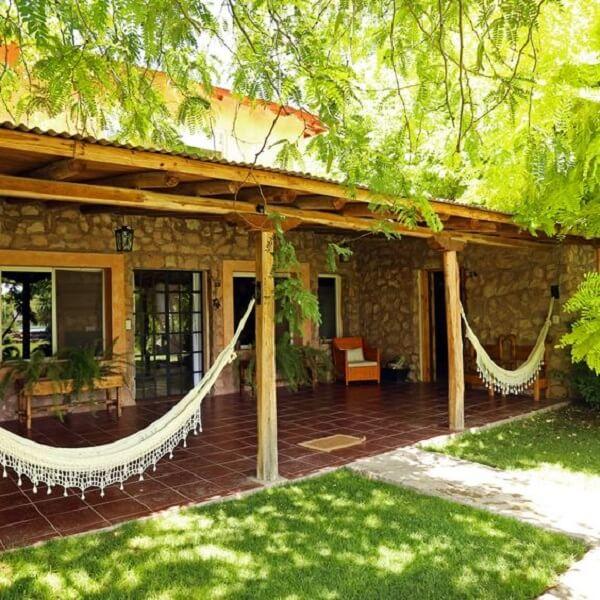 O revestimento externo feito de pedras realça a beleza dos projetos de casas de campo rústicas com varanda