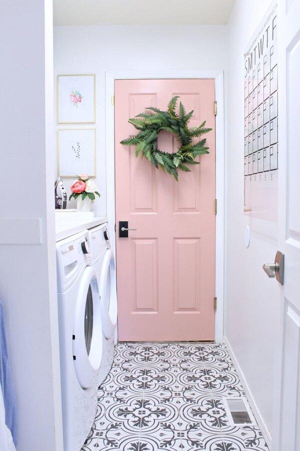 Os quadros delicados e a porta rosa deixaram a área de serviço simples charmosa