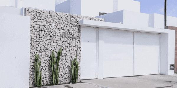 Pedra de muro portuguesa acinzentada na fachada se conecta com o portão branco