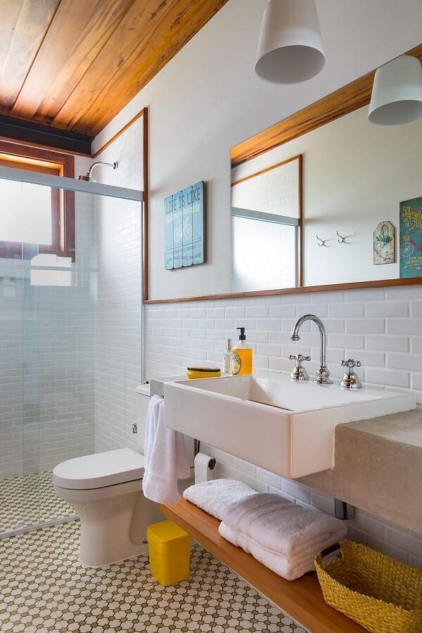 Piso com ladrilhos, forro de madeira no teto e chuveiro cromado decoram o ambiente