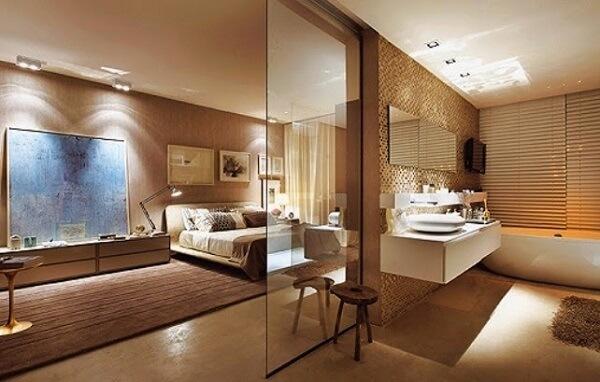 Tons terrosos decoram esse quarto com suíte de vidro