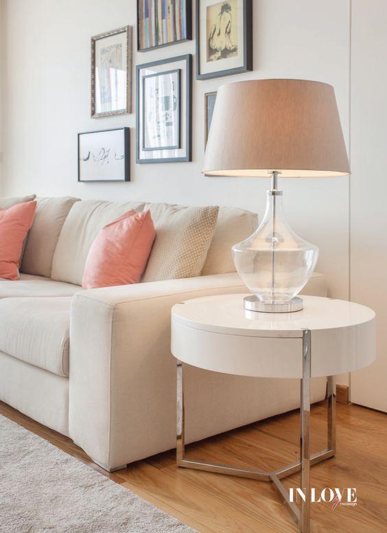 Sofá bege com almofada rosa claro e abajur combinando