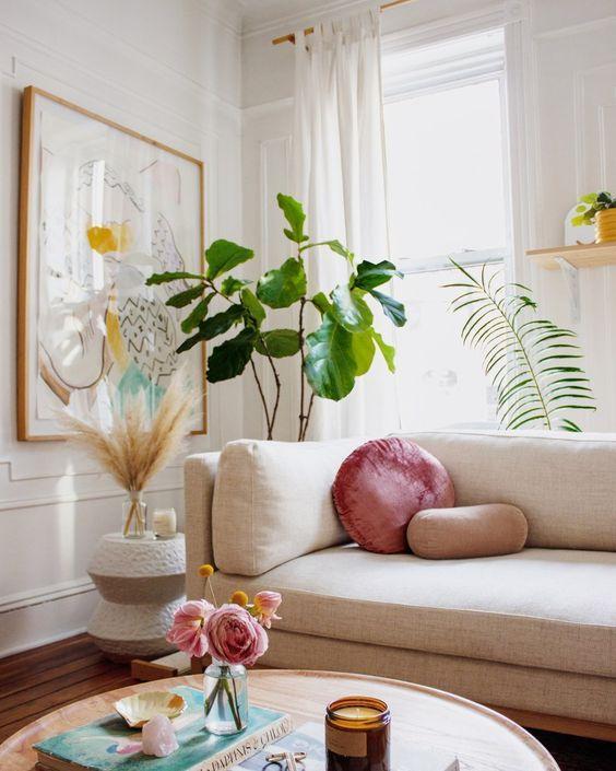 Almofada rosa e redonda no sofá bege