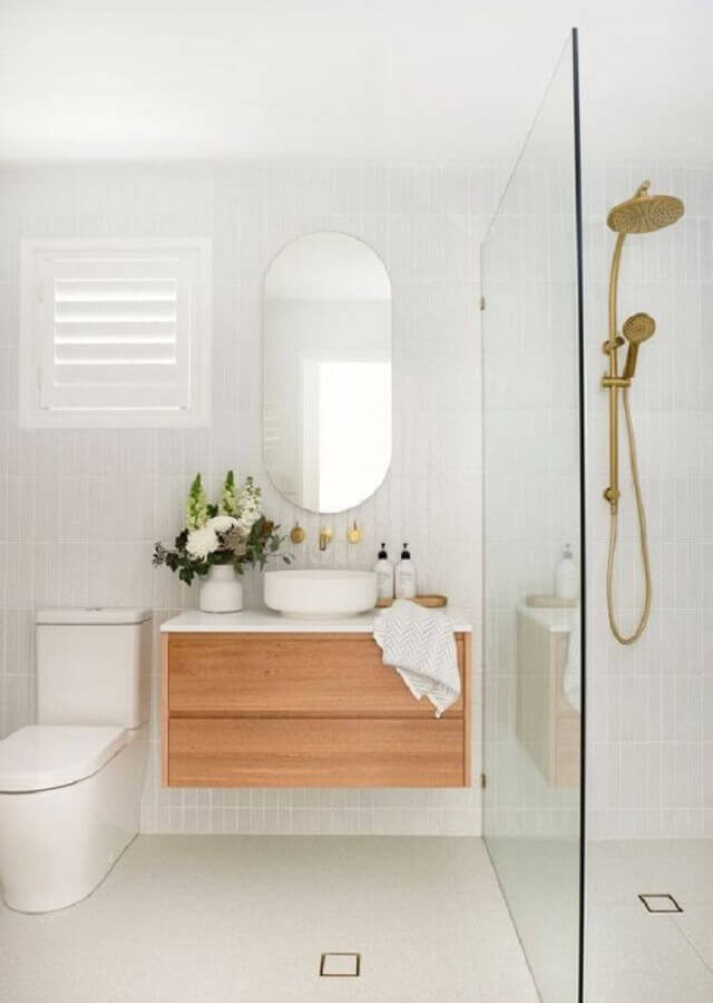 banheiro minimalista branco decorado com espelho oval e gabinete de madeira Foto Casa de Valentina