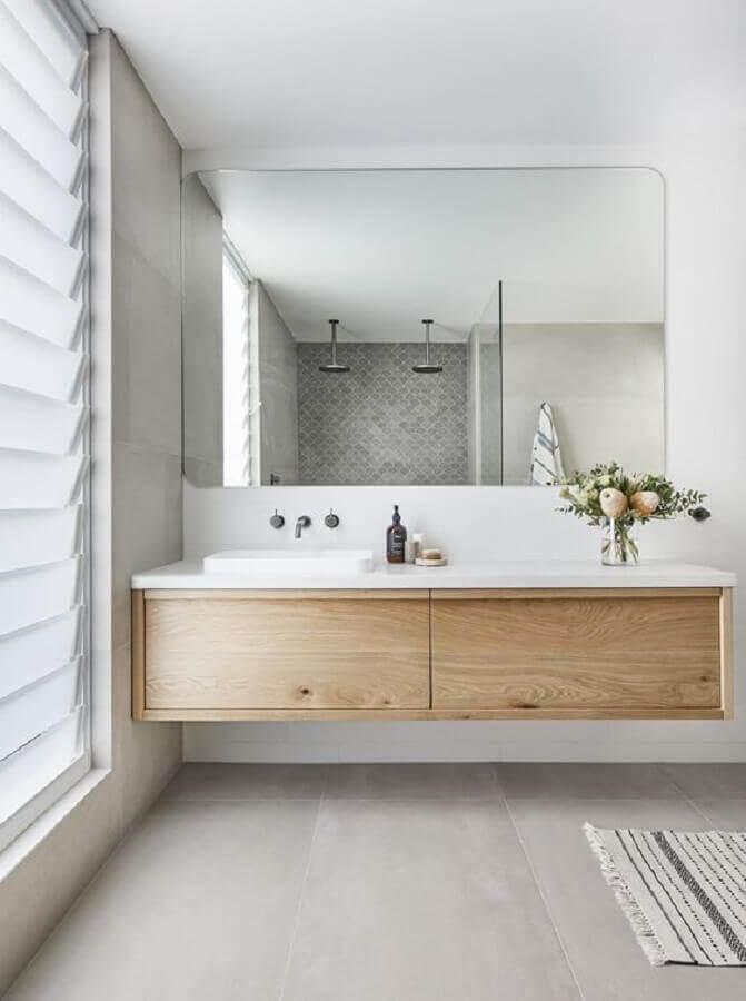 banheiro minimalista branco decorado com gabinete de madeira suspenso Foto Jeito de Casa