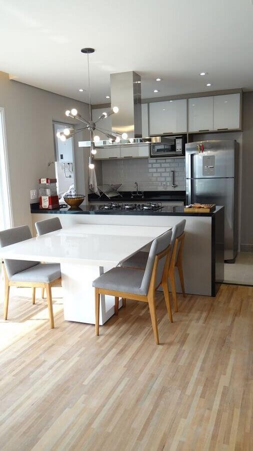 cozinha e sala de jantar integradas com mesa integrada à bancada Foto Arkpad