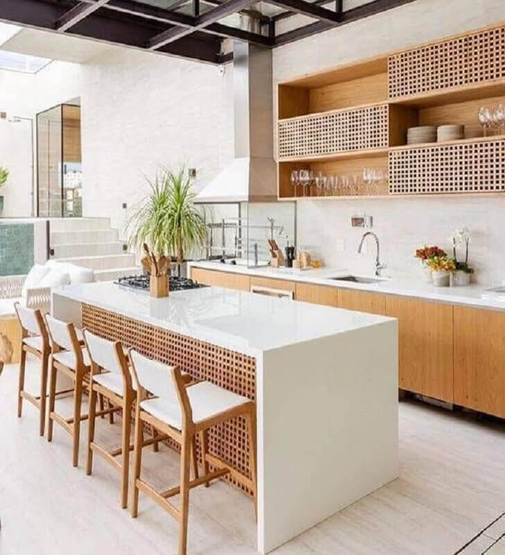 cozinha gourmet externa com ilha branca e armários de madeira Foto Jeito de Casa