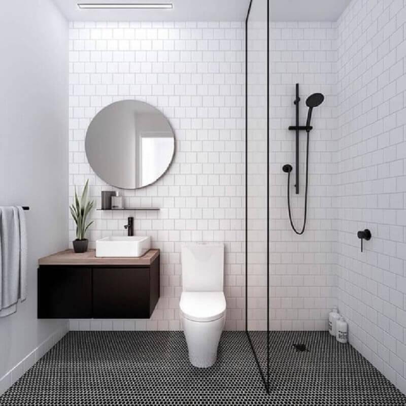 decoração banheiro minimalista pequeno com espelho redondo e gabinete preto suspenso Foto Archzine