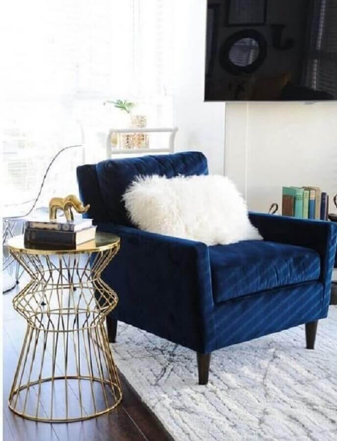 decoração de sala com poltrona azul escuro e mesa lateral dourada  Foto Apartment Therapy